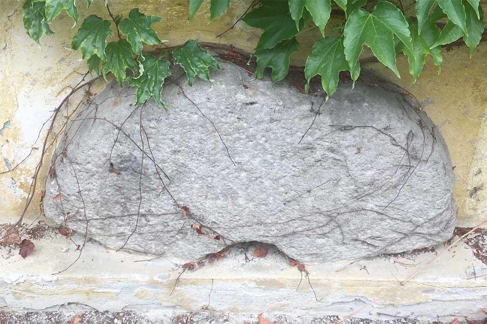"""Dieser Mühlstein wurde bei Abbruch einer Hauptmauer des """"Herrenhauses"""" gefunden, stammt vermutlich von der Winkelmühle und befindet sich auf der Nordseite vom """"Magazin""""."""
