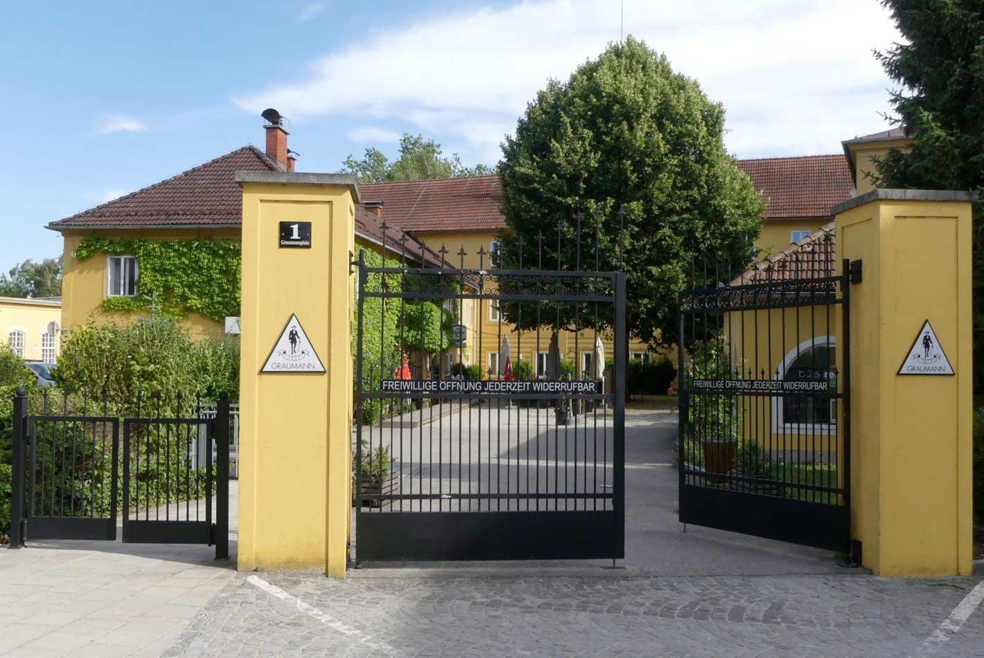 """Fabrikseinfahrt, dahinter """"Herrenhaus"""" mit Lindenhof."""